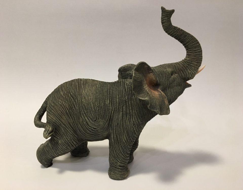 Beeldje van een levensechte olifant met de slurf omhoog