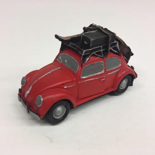 Stenen beeld auto Volkswagen kever met bagage en ski's rood