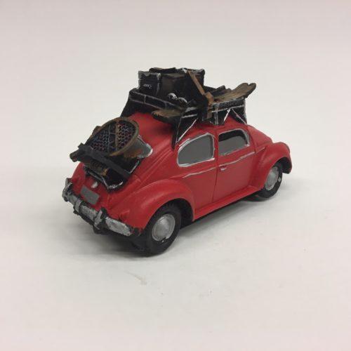 Stenen beeld auto volkswagen kever met bagage en ski's in rood