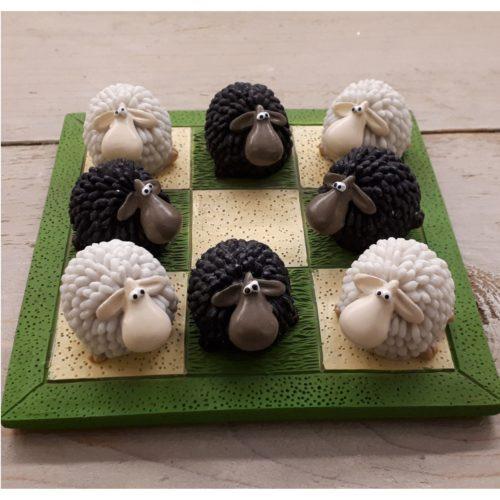 Spel boter kaas en eieren met witte en zwarte schapen