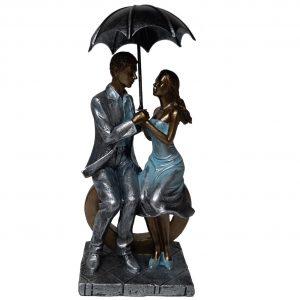 Beeld liefde man en vrouw met paraplu zittend op een hart