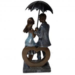 Beeld liefde man en vrouw met paraplu zittend-