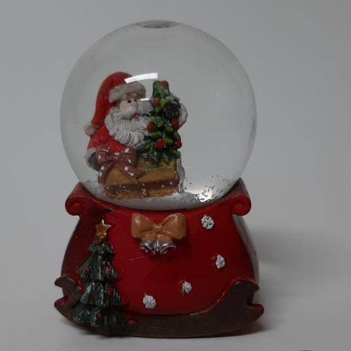 Sneeuwbol cadeauzak op arrenslee en kerstman op cadeau met kerstboom