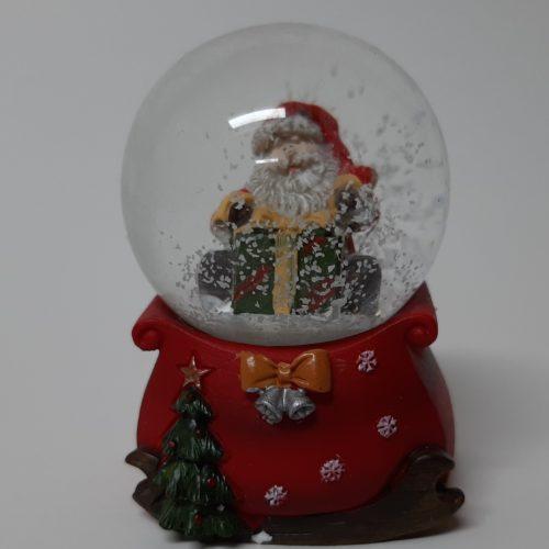 Sneeuwbol cadeauzak op arrenslee en kerstman op groen-rood cadeau