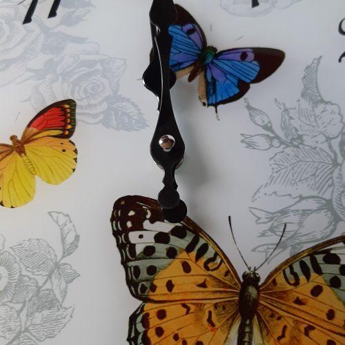 Klok van glas met vlinders op een witte achtergrond