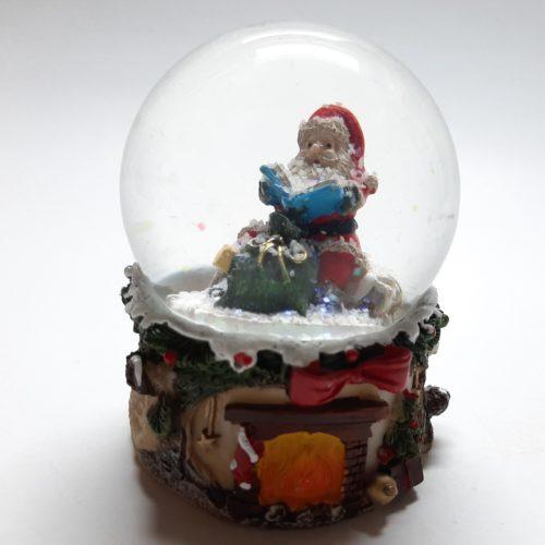 Sneeuwbol haardvuur met strik en lezende kerstman 9cm hoog