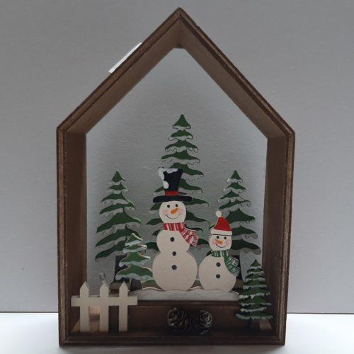 Kerst decoratie houten huis met sneeuwpoppen in winters tafereel